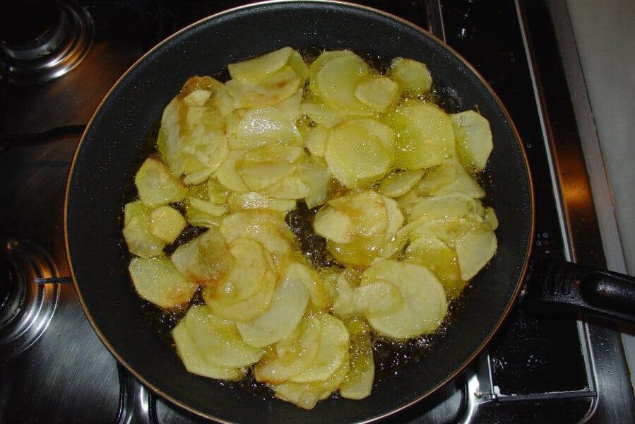 Para hacer patatas panaderas, corta la patata por la mitad longitudinalmente. Trocea en láminas finas.