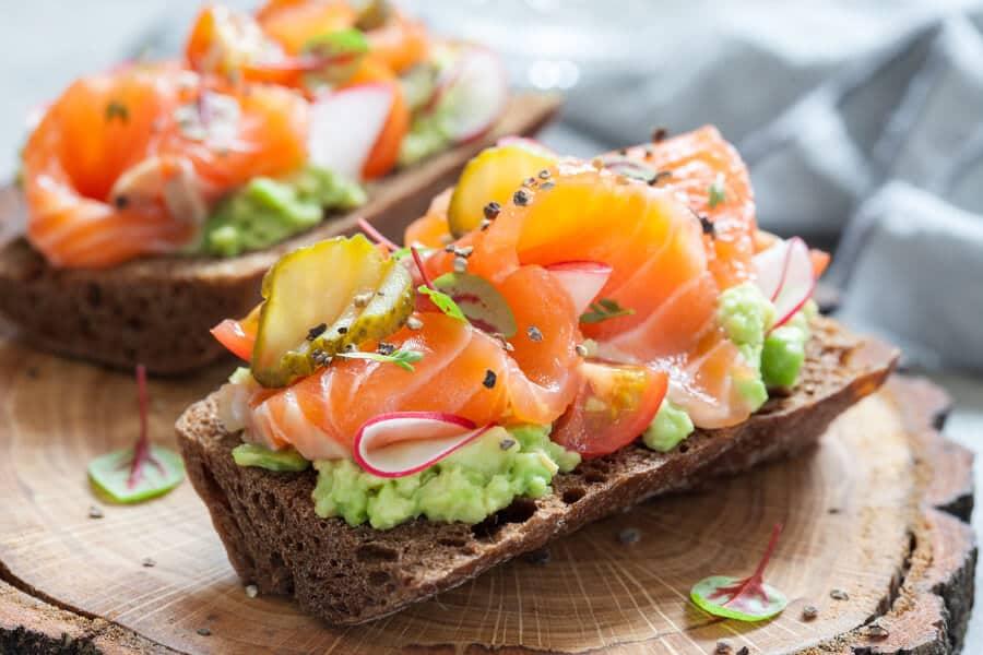 Sándwich Smorrebrod con salmón, verduras y hierbas