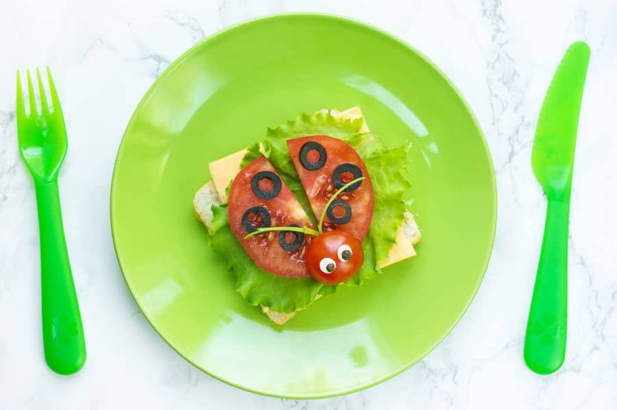 Plato infantil saludable: Mariquita de tomate con aceitunas sobre pan tostado con queso y lechuga